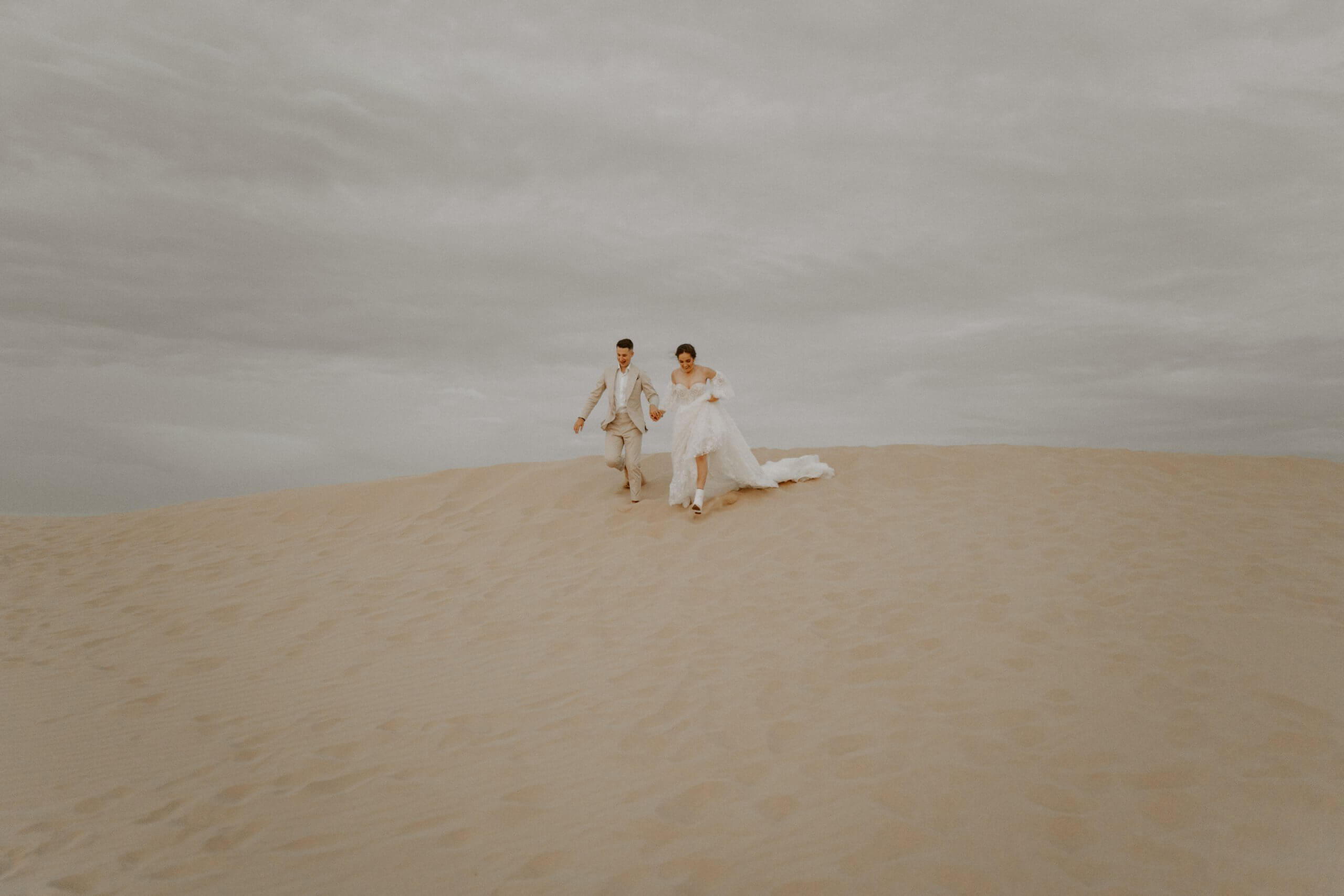 Couple dressed in wedding clothes running down sand dunes, Wilsons Prom Sand Dunes Elopement